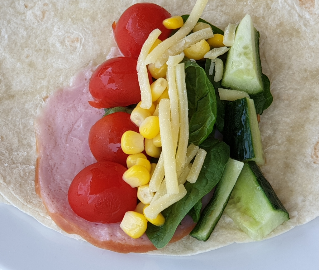 The ingredients for a healthy burrito - lean ham, tomatoes, corn, spinach, cucumber, low fat shredded cheese, tortilla